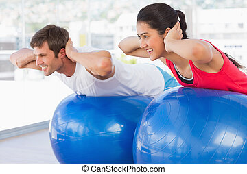 Fit couple exercising on fitness balls in gym - Fit young...