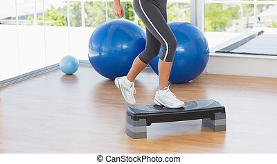 Low section of a fit woman performing step aerobics exercise...