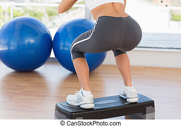 Low section rear view of a fit woman exercising on step -...
