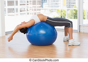 Fit woman stretching on exercise ball at gym - Side view of...
