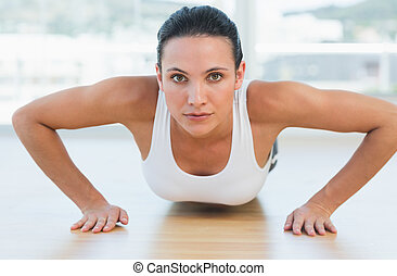 Determined beautiful woman doing push ups in gym -...