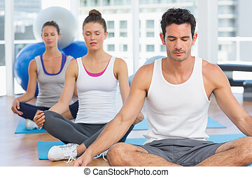 People in meditation pose with eyes closed at fitness studio...