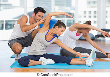 Women doing stretching exercises as trainer helps one at...