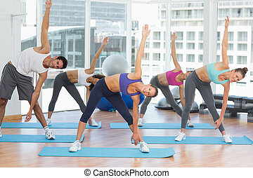 Sporty people stretching hands at yoga class - Full length...