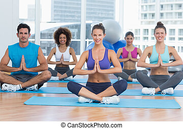 People in Namaste position smiling at fitness studio -...