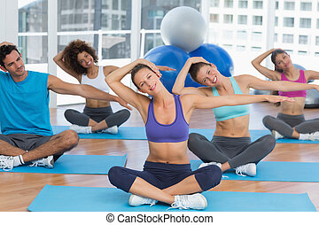 People with trainer doing pilate exercises - Young people...