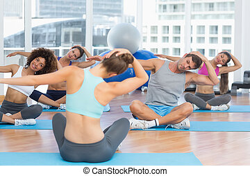 People with trainer doing pilate exercises in a bright gymYoung