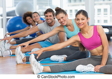 Sporty people stretching hands to legs in fitness studio -...