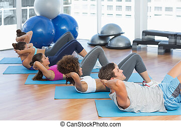 Determined people doing sit ups in fitness studio