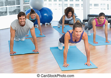 People doing push ups in fitness studio - Smiling young...
