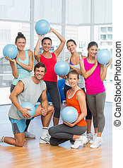 Fit young people with balls in exercise room - Portrait of...