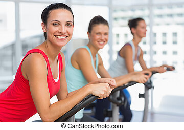 Fit young people working out at spinning class - Side view...