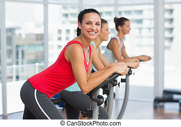 Fit people working out at spinning class - Side view...