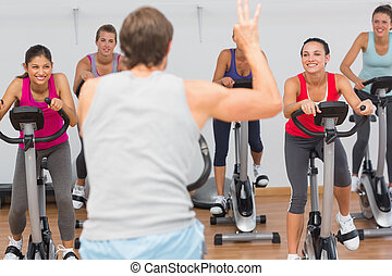 Trainer and fitness class at spinning class - Male trainer...