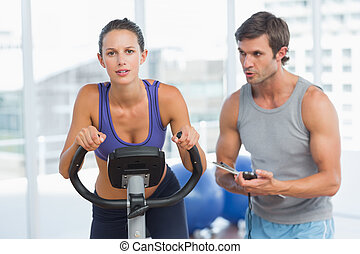 Trainer watching woman work out at - Male trainer watching...