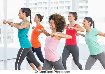 Fitness class and instructor doing pilates exercise -...