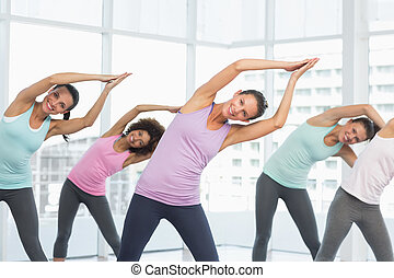 Smiling women doing pilate exercises in fitness studio -...