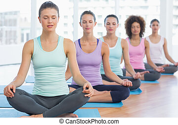 Sporty women in meditation pose with eyes closed - Sporty...