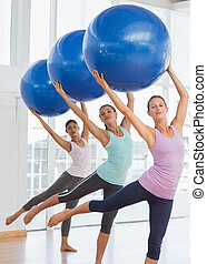 Fitness class doing pilates exercise with fitness balls -...