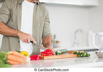 Mid section of a man chopping vegetables in kitchen - Mid...