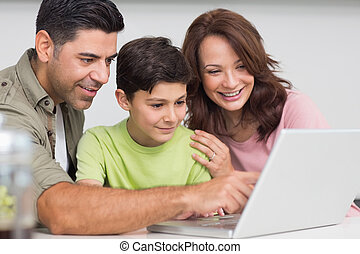 Smiling couple with son using laptop - Smiling couple with...