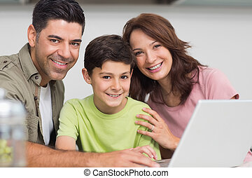Smiling couple with son using lapto - Portrait of a smiling...