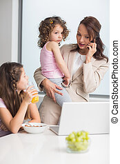 Well dressed mother with daughters and laptop in the kitchen...