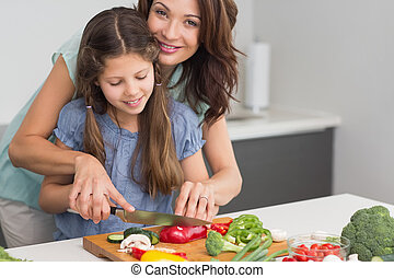 Smiling woman with daughter chopping vegetables in kitchen -...