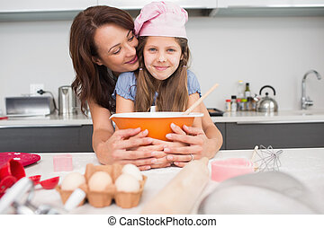 Girl and mother preparing cookies in kitchen - Portrait of a...