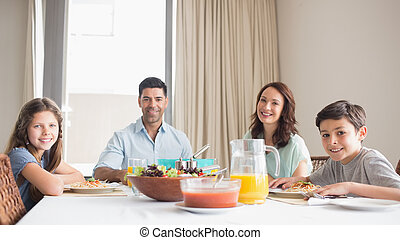 Portrait of happy family of four sitting at dining table in...