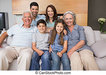 Portrait of smiling extended family on sofa in living room -...