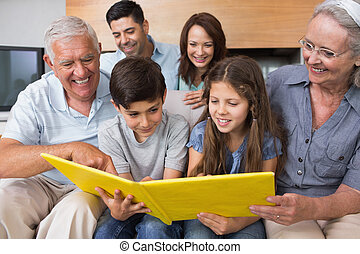 Extended family looking at album photo in living room -...