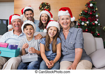 Portrait of extended family in Christmas hats with gift boxes in the living room at home