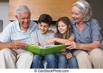 Happy grandparents and grandkids looking at album photo in...
