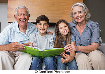 Portrait of grandparents and grandkids looking at album...