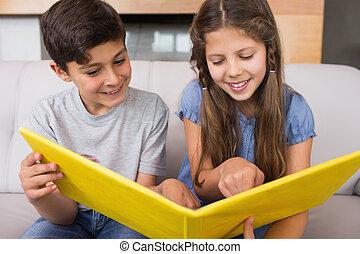 Smiling siblings looking at photo album in living room