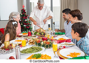 Extended family at dining table for christmas dinner in the...