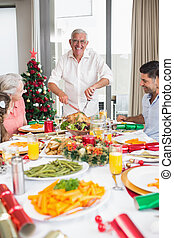 Cheerful family at dining table for christmas dinner