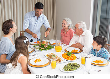 Extended family at dining table in house - Extended family...