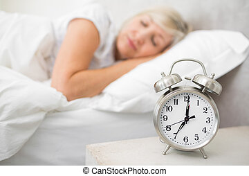 Woman sleeping in bed with alarm clock in foreground at...