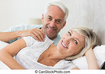Closeup of a smiling mature couple lying in bed - Closeup...