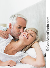 Mature man kissing womans cheek in bed - Closeup of a mature...
