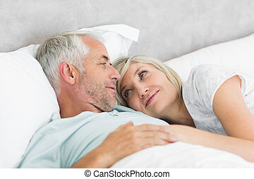 Loving mature couple lying in bed - Closeup of a loving...