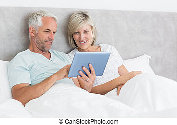 Happy couple using digital tablet in bed - Happy mature...