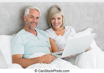Happy mature couple using laptop in bed - Portrait of a...