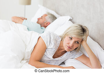 Tensed woman lying besides man in bed - Closeup of a tensed...