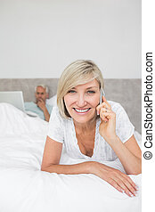 Happy woman using cellphone while man using laptop in bed -...