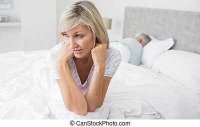 Tensed mature woman sitting in bed with man in background -...