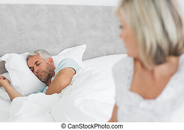 Tensed mature woman sitting in bed - Closeup of a tensed...