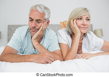 Closeup of displeased mature couple lying in bed - Closeup...